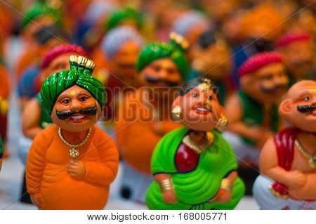 Bobble heads of caricatures of indian men with moustaches and turbans and women in a saree