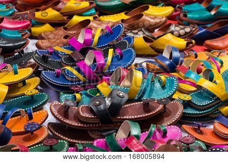 Pile of colorful handmade leather slippers spread out on a sidewalk for selling