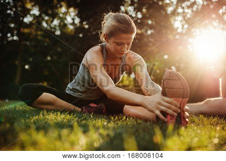 Healthy young woman exercising at park. Fit young woman doing training workout in morning.