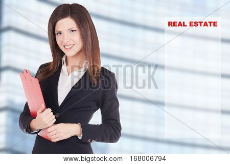 young woman real estate agent in front of a building