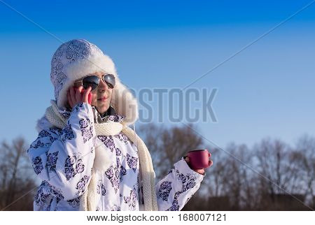Little girl using her phone on a sunny winter day. Smiling little girl with a pink cup of hot drink. Glamour little girl talks on phone. Caucasian stylish little girl in winter clothes and sunglasses.
