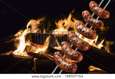 Sausages On The Barbecue Spit With Flames