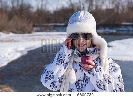 Little girl speaks by cell phone close up.Caucasian stylish little girl with a pink cup of hot drink in winter day. Glamour little girl talks on phone. little girl speaking by pink smartphone outdoor