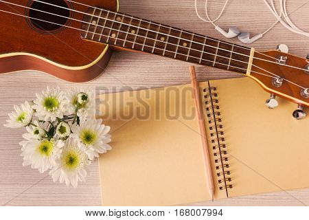 Top View Ukulele And Blank Note Book With Pencil And Flower For Love Music Concept