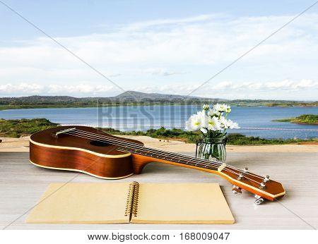 Ukulele And Blank Note Book And Flower On Lake Background