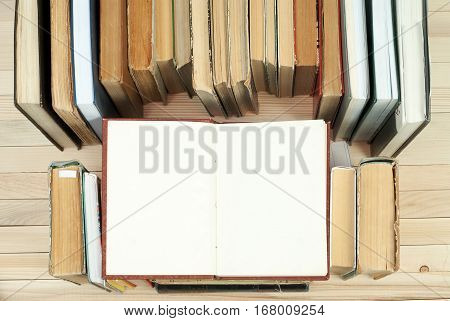 Pile of books. Open book hardback books on wooden table. Knowledge is important. Copy space. Top view.