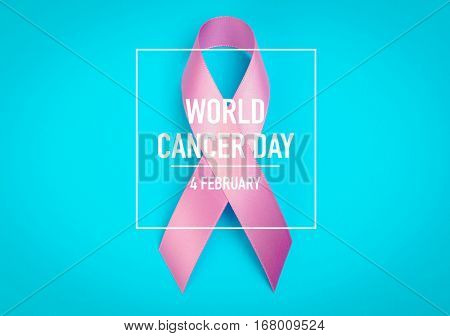 World cancer day : Breast Cancer Awareness Ribbon on blue Background