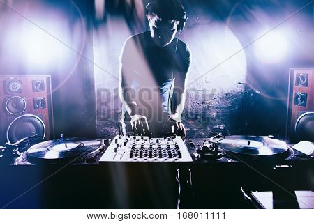 Club DJ playing mixing music on vinyl turntable at party wearing sunglasses with lens flare from nightlife lights.