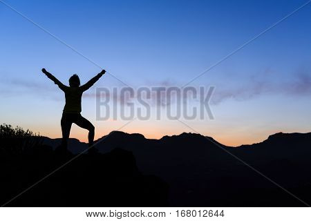Woman hiking silhouette in mountains sunset and ocean. Female hiker climber or trail runner with arms outstretched on mountain top looking at beautiful night sunset inspirational landscape.