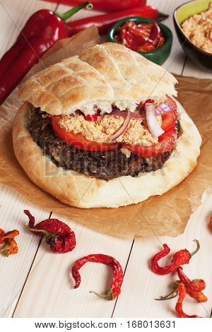 Pljeskavica, serbian ground beef burger with tomato, onion and urnebes salad