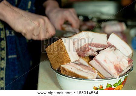 man cuts the raw lard for salting