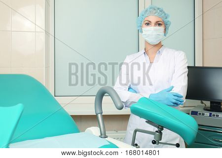Gynecologist in room with chair at modern hospital