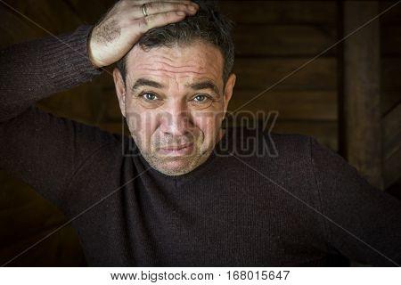 Bad news. Sad surprised man holding his hand behind his head. Dark background.