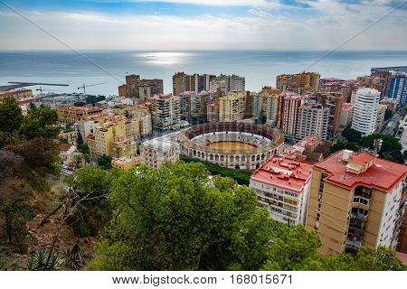 Wide angle view of Malaga city and bullfight arena near mediterranean sea