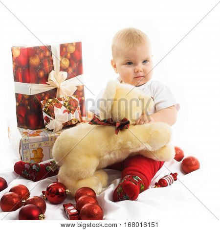 Happy, cute Christmas baby with baubles and gifts isolated on white.