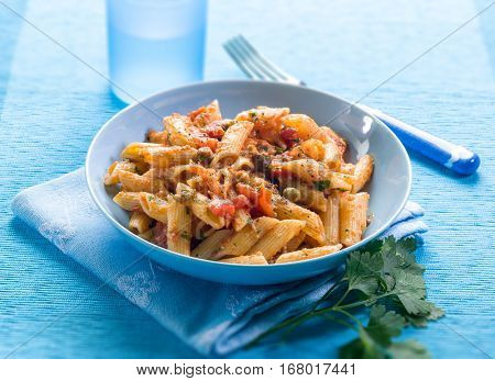 pasta with anchovies capers and tomatoes, selective focus