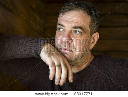 Sad mature man. His hand under his chin.