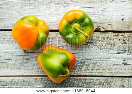 Multicolored bell pepper on old wooden table. Top view.