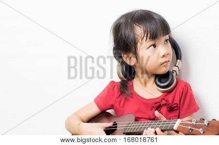 Japanese girl is playing guitar and wearing headphone. Little Asian artist looking firm and confidence with her music instrument. Little asian musician with guitar headphone isolated on white.