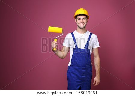 Handsome young worker with paint roller on color background