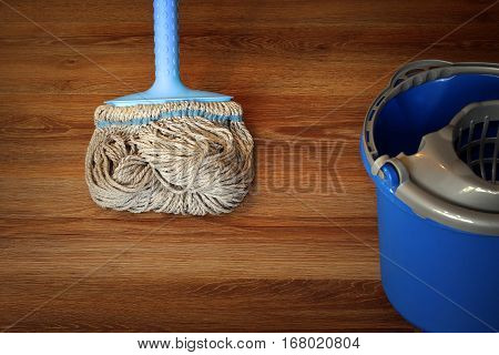 cleaning equipment on wooden floor mop and blue bucket