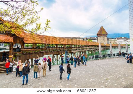 Lucerne Switzerland - 15 May 2016: People walking and taking pictures at the famous historic wooden Chapel bridge in Lucerne Switzerland.