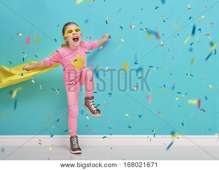 Little child plays superhero. Kid on the background of bright blue wall. Girl is throwing confetti and jumping. Yellow, pink and  turquoise colors.