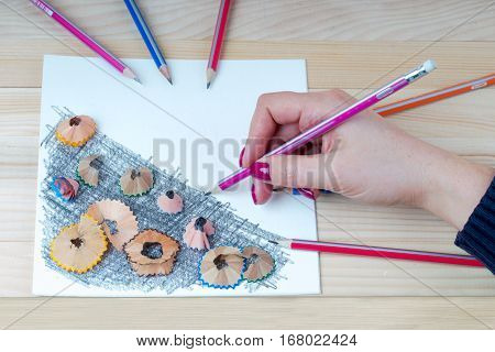 A hand is holding a pencil. Pencil sharpener shavings on the white paper. Back to school