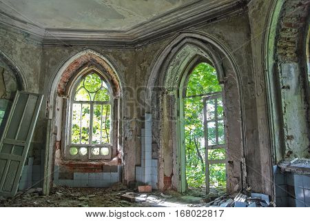 Old room with rotten window and doorway of an abandoned mansion of Khvostov in gothic style, Lipetsk region