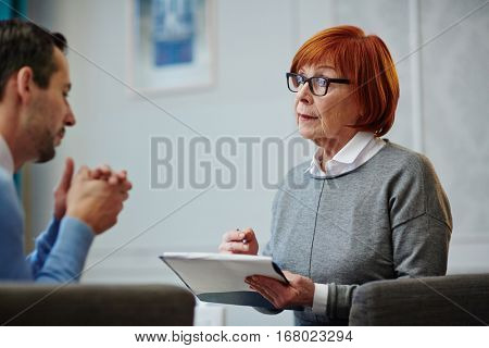 Serious counselor listening to her patient and writing down his problems