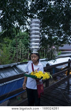 Kanchanaburi Thailand - January122017 : Unidentified Mon girl carries pots on her head and sell flower to make merit in Sangklaburi Kanchanaburi Thailand