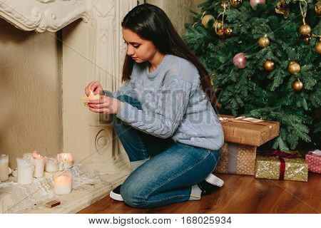 young beautiful woman ignites a candle near a Christmas tree. Studio horizontal close-up portrait.