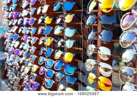 Bright sunglasses in the window of a street shop on the waterfront of resort town
