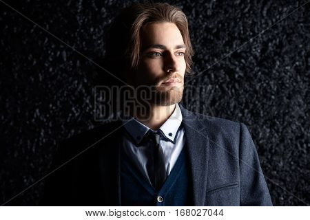 Close-up portrait of a handsome man wearing elegant classic suit. Male beauty, fashion. Hairstyle. Studio shot.
