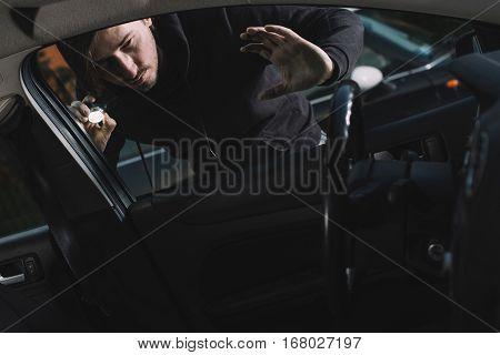 Auto Thief Looking To Car Interior