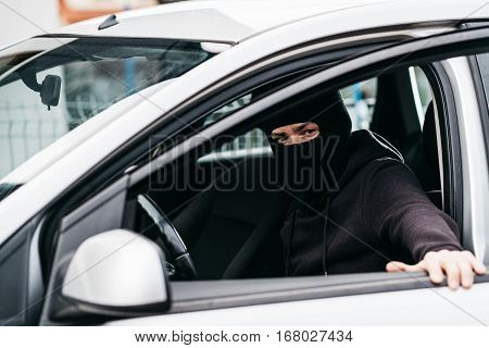 Auto Thief In Black Balaclava Closing Door Of Stolen Car