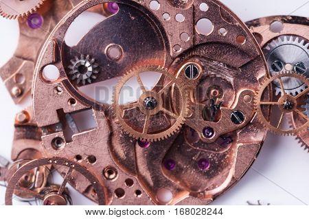 Parts of broken watch mechanism with gearwheel and springs