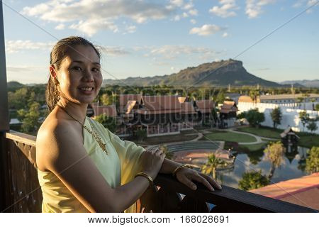 Portrait of woman dressing in Thai traditional costume with ancient town background