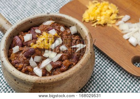 Delicious chili topped with onions and cheese on a cutting board.