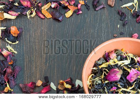 Leaves of tea scattered on the dark wooden background