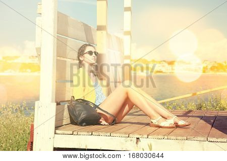 Young Girl Relaxing by the Sea. Summer Vacation Daydream. Retro Toned Photo with Bokeh and Copy Space.