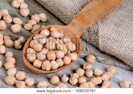 Chickpeas in a wooden spoon and jute canvas on table