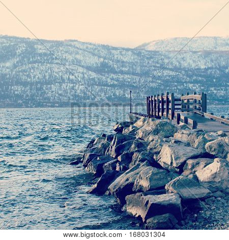 Dock And Rocks On Lake In Winter