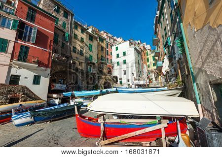 RIOMAGGIORE, ITALY - DECEMBER 2016: Village of Riomaggiore town with color houses and moored boats. Riomaggiore is a popular turistic town in Cinque Terre national park in Italy.