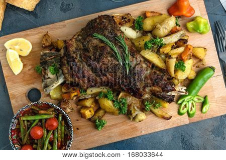 Roast shoulder of lamb on baked potato and carrots, wooden board, top view.