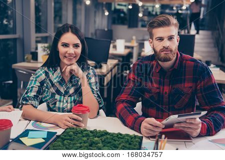 Portrait of two young happy freelancers on financial training sitting on modern openspace workplace with desktop