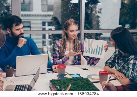 Young woman explaining diagrama of financial growh on meeting sitting at desktop