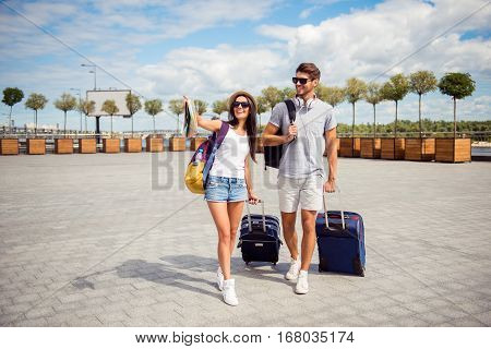 Two Smiling Young  Lovers With Valise Walking From Airport In Town