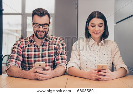 Cheerful Happy Colleagues Writing Messages On Mobile Phones