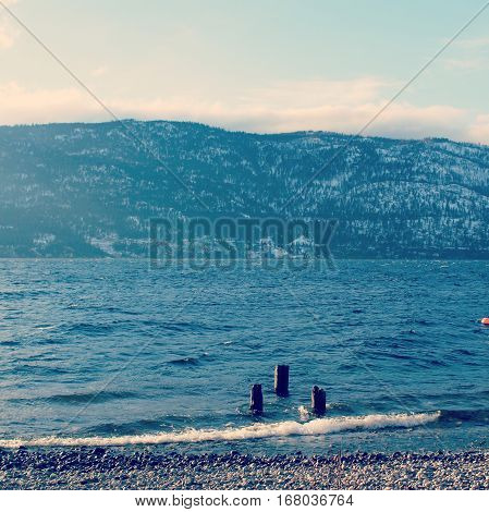 Winter landscape scene of lake and mountains with three posts in water on shore. Waves along shore line of rocky beach. Snow covered mountains lake and bright sky in background.